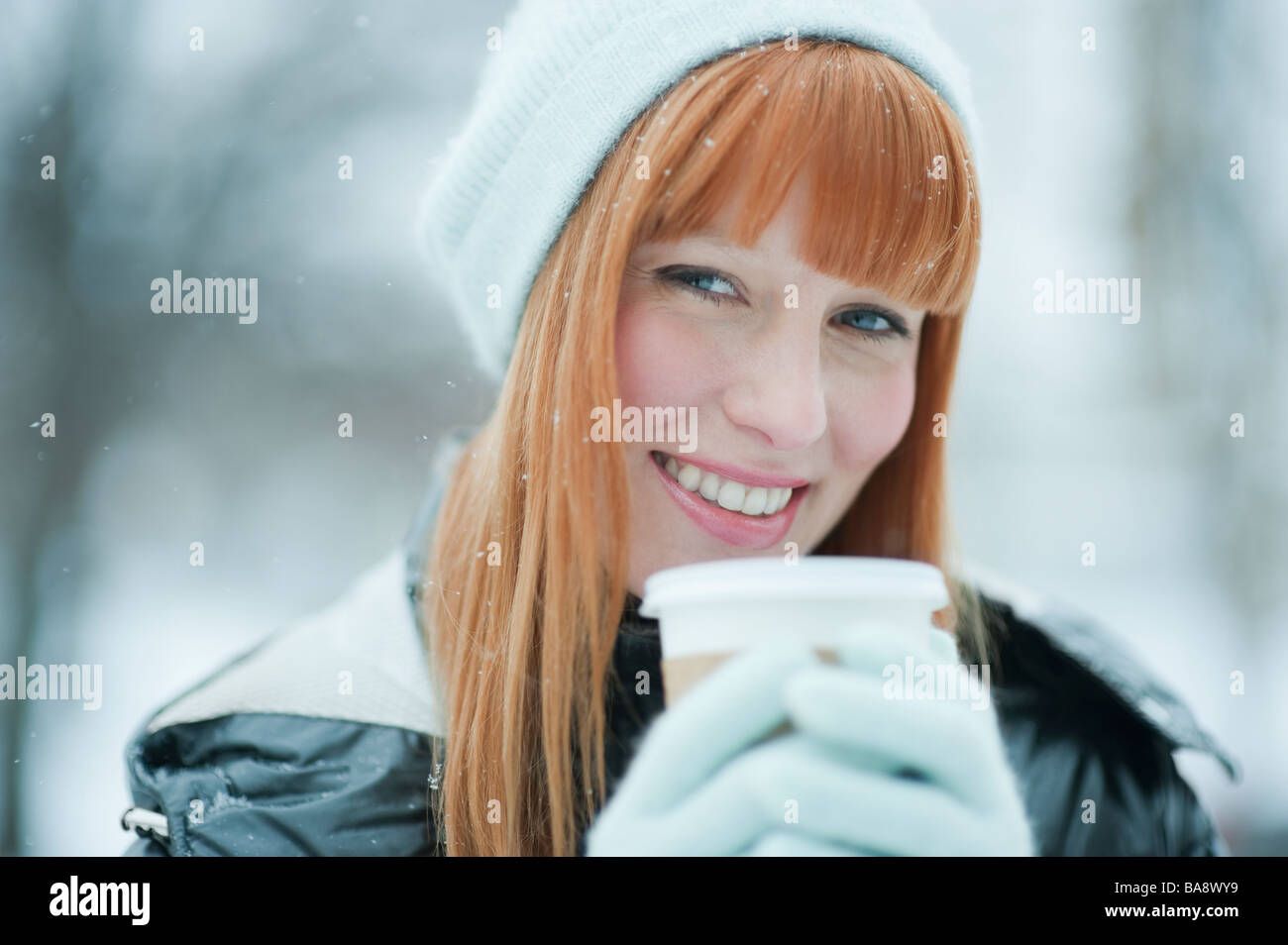 Woman drinking coffee in snow - Stock Image