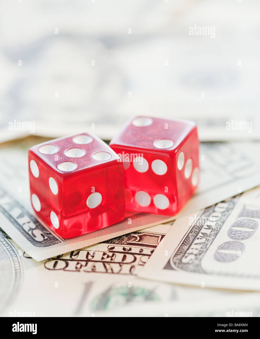 Dice on pile of money - Stock Image