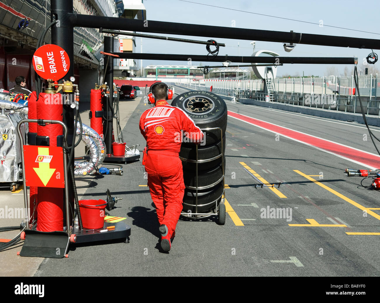 Ferrari mechanic puhes stack of race tyres along pit lane at racetrack at Formula One testing sessions - Stock Image