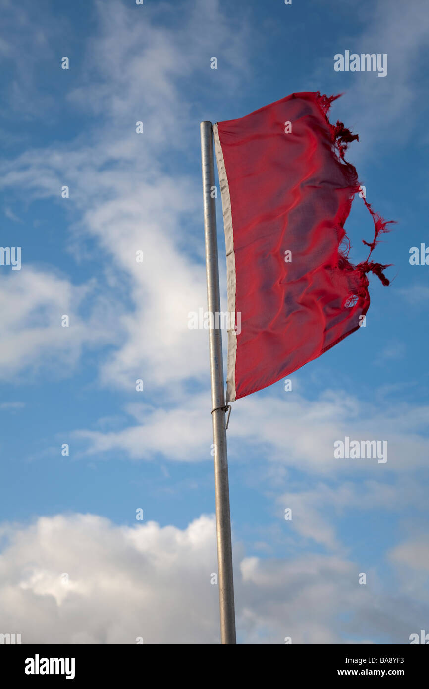 Ragged flag in high wind - Stock Image