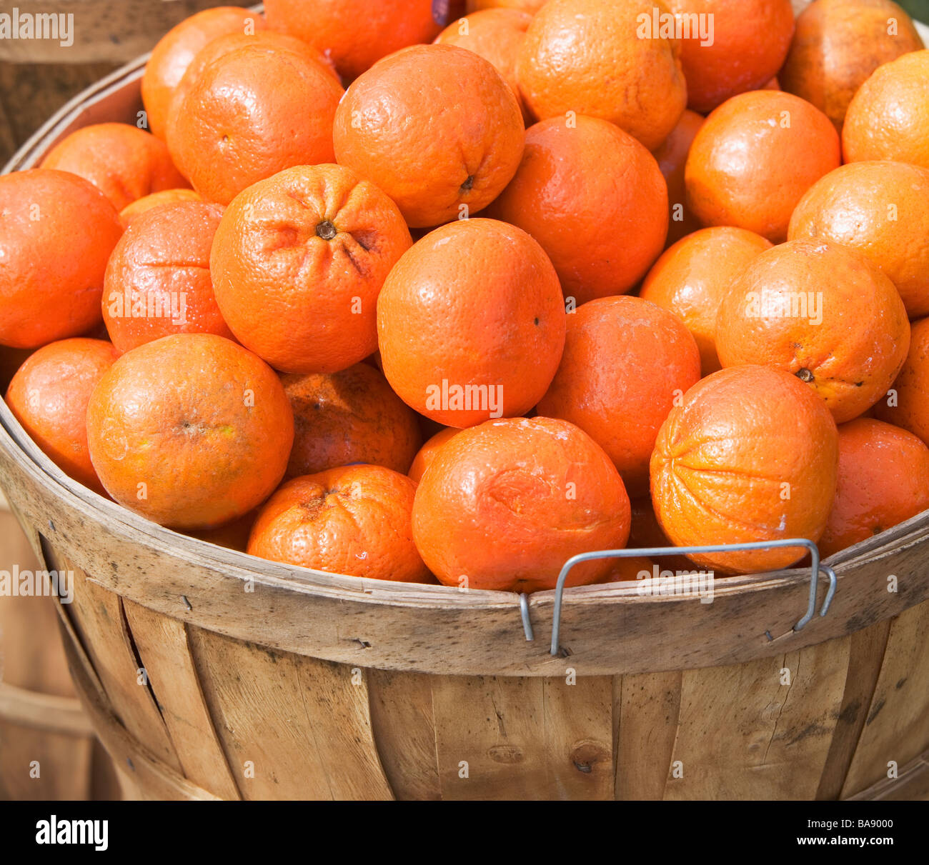 Oranges in a basket at a fruit stand - Stock Image