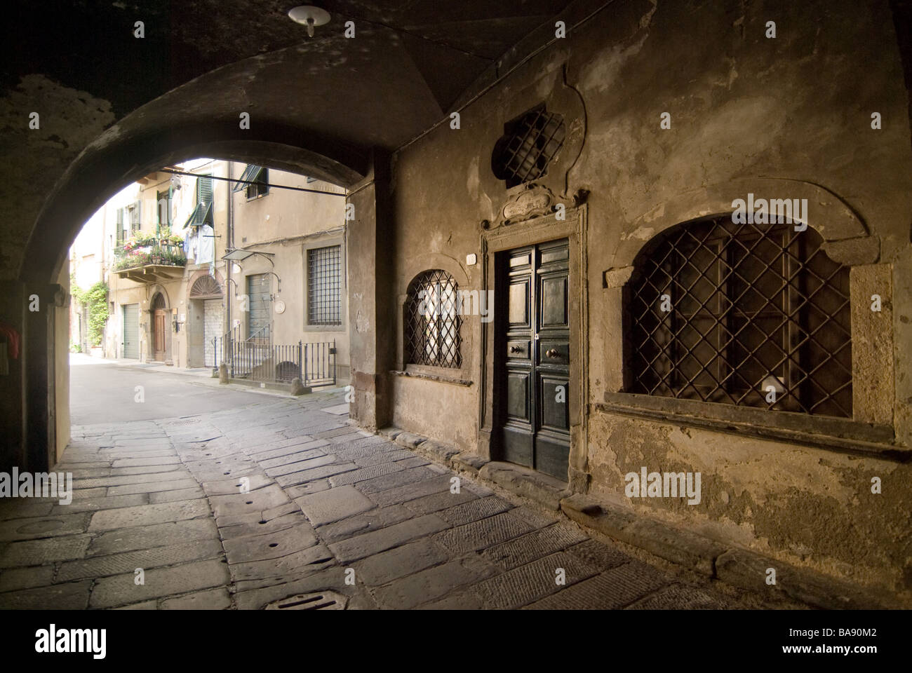 photograph of old cobbled street under archway in Lucca - Stock Image
