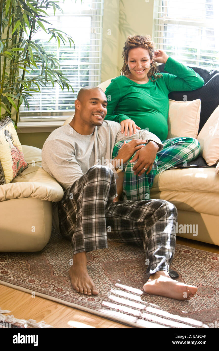 African American Living Room Apartment Decor: African-American Couple Sitting In Living Room Wearing