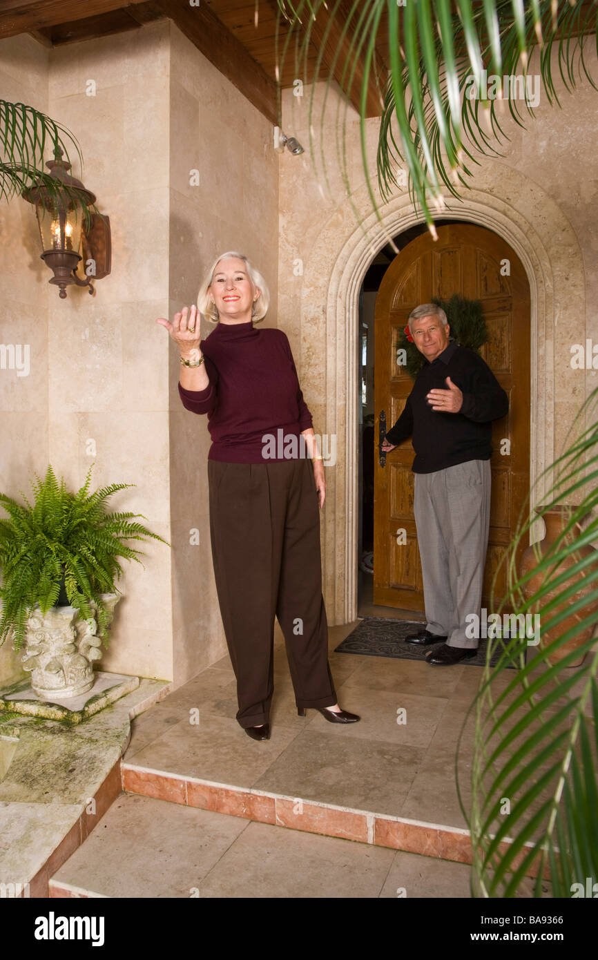Portrait of senior couple standing in front of luxurious home Stock Photo
