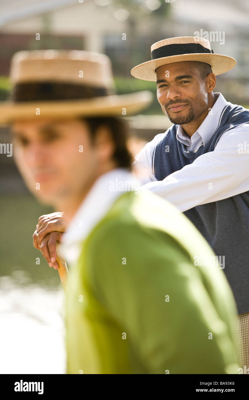 Portrait of 1920s socialite men relaxing at garden party on water's edge - Stock Image