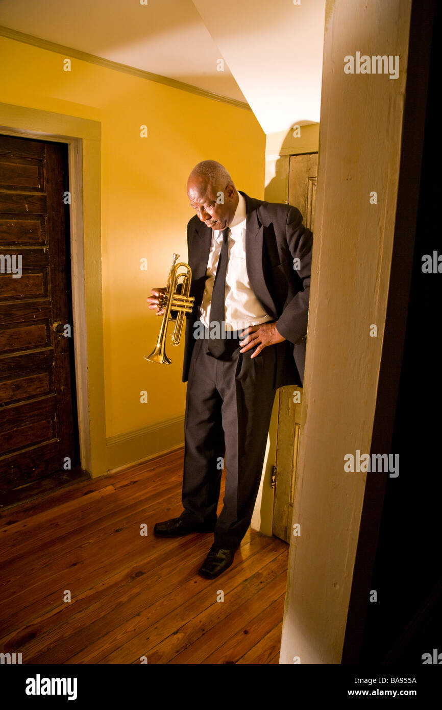 Senior African American jazz musician standing in hallway with trumpet - Stock Image