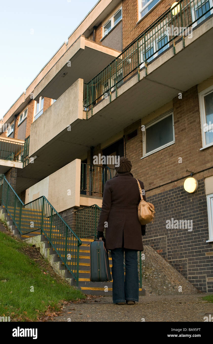 lady standing outside a block of council flats with suitcase Stock Photo