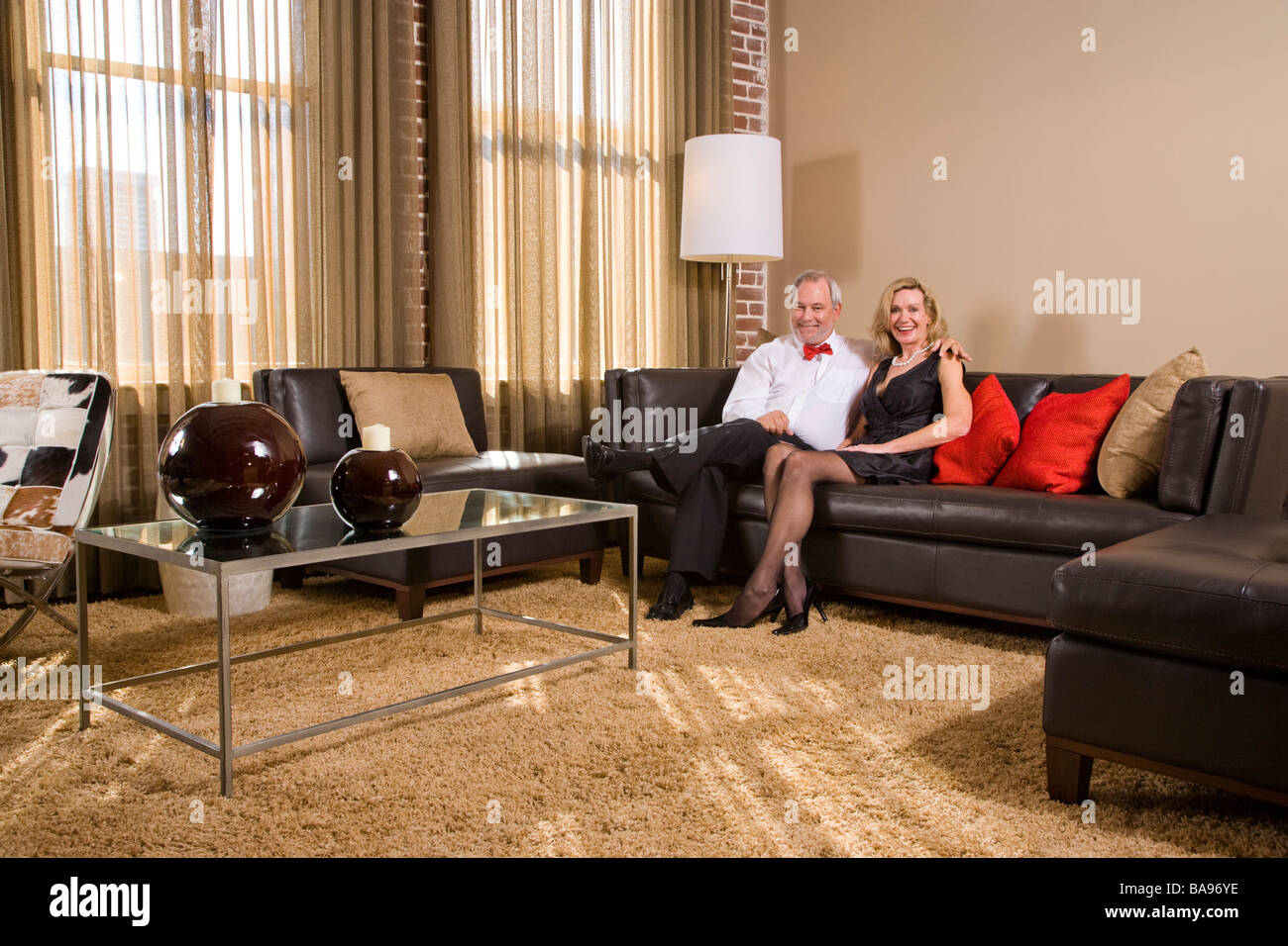 Middle-aged couple sitting on couch in living room - Stock Image