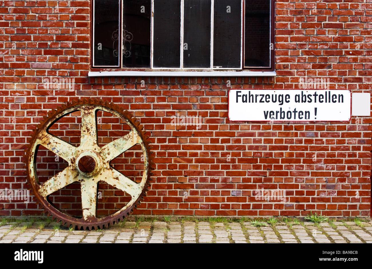 huge rusty gear in front of brick wall of workshop at UNESCO world heritage site Zollverein coal mine industrial - Stock Image