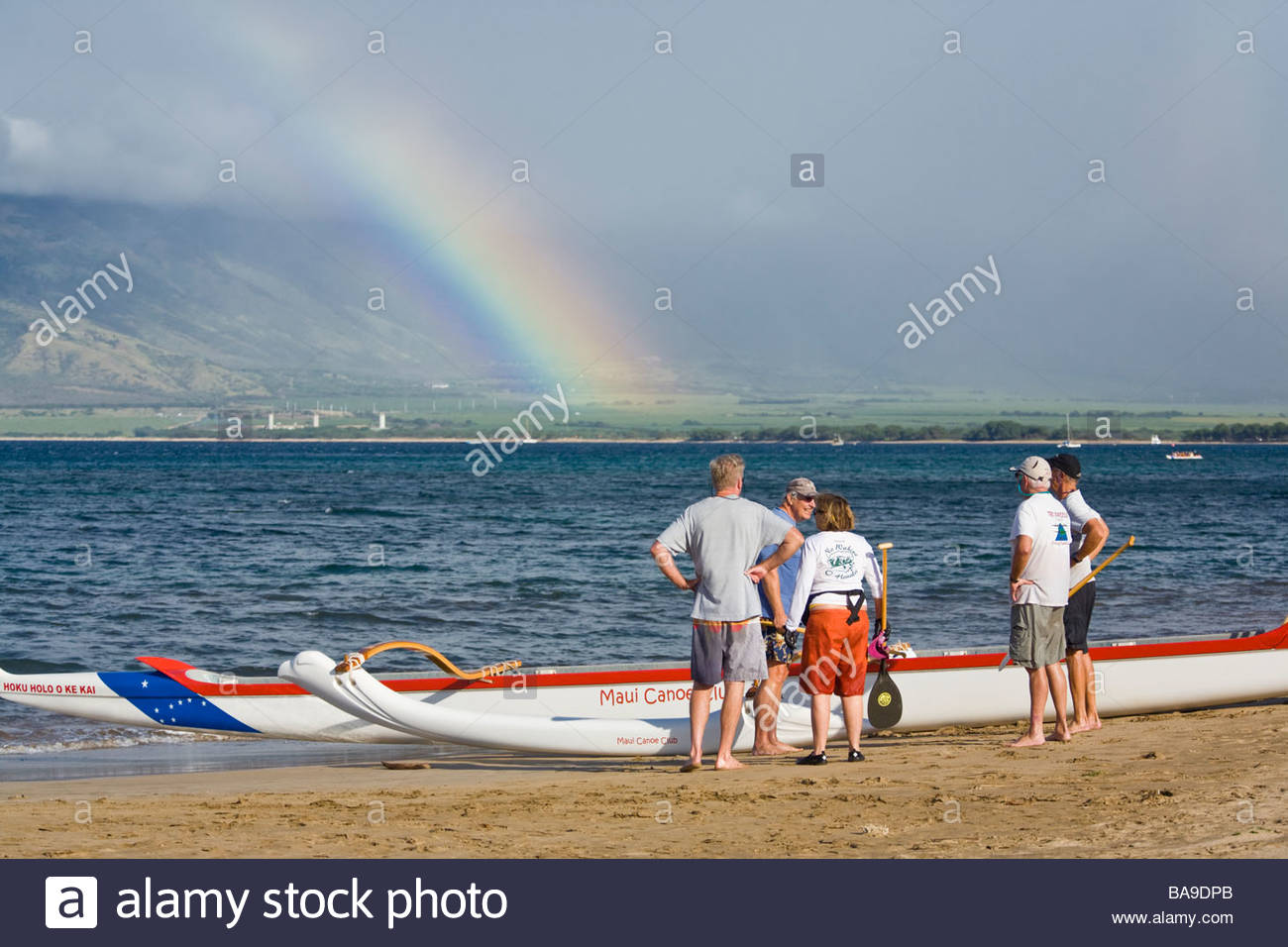 Outrigger canoe and seniors tour group on beach at Kihei on the island of Maui in the state of Hawaii USA - Stock Image