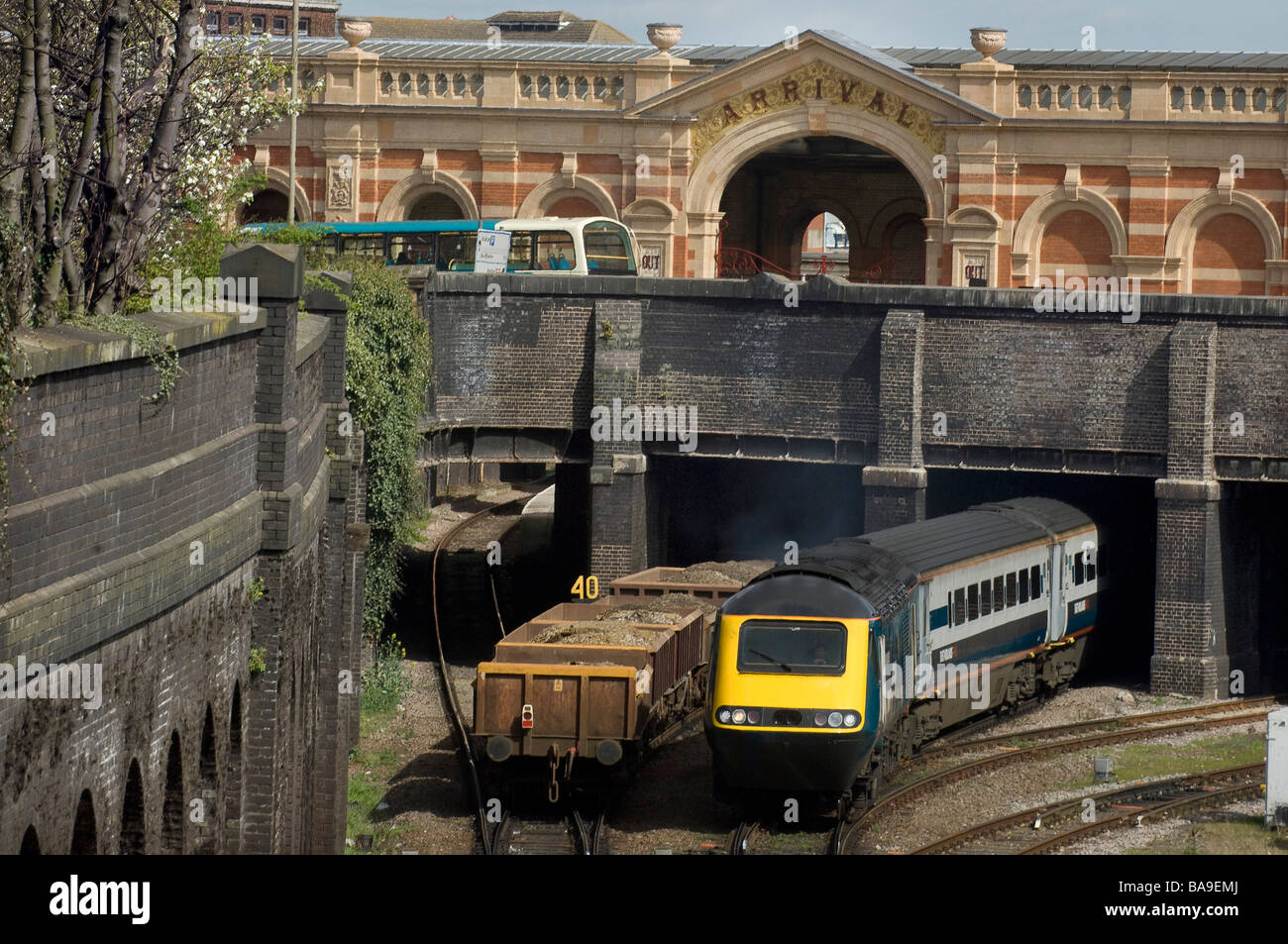 A freight train going under a bridge as a passenger train emerges and a bus is seen on the road above - Stock Image