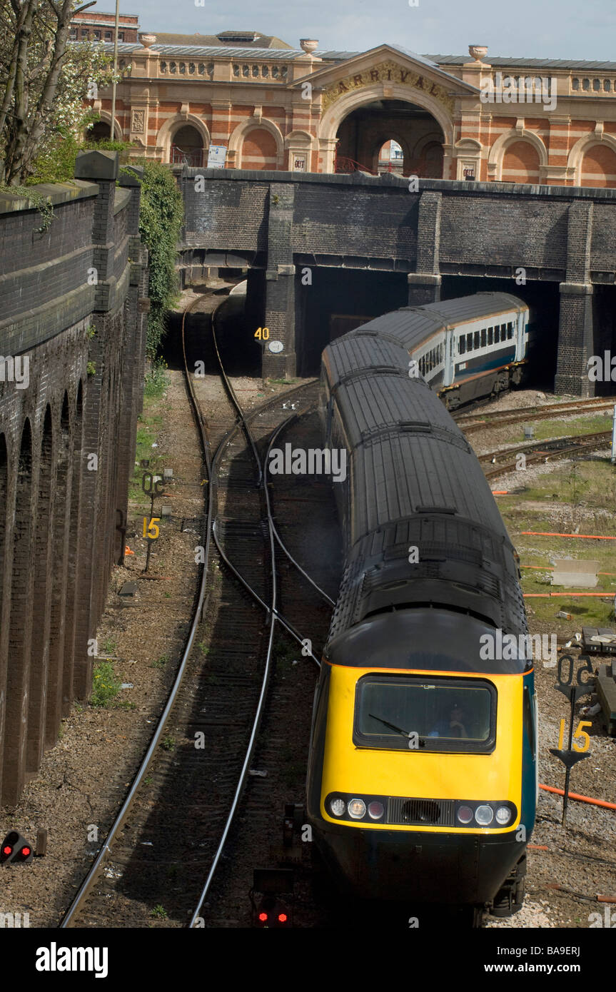 Train emerging from tunnel and snaking along railway track - Stock Image