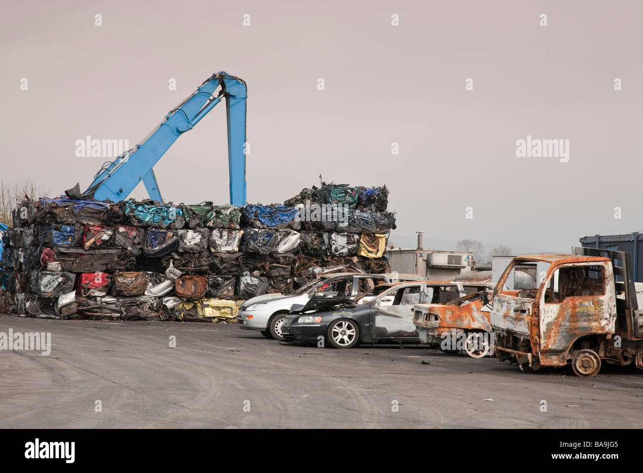Damaged vehicles in scrapyard with pile of crushed vehicles. Stock Photo