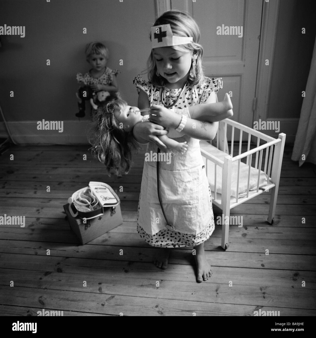 Girl play doctor taking care of a doll, Sweden. - Stock Image