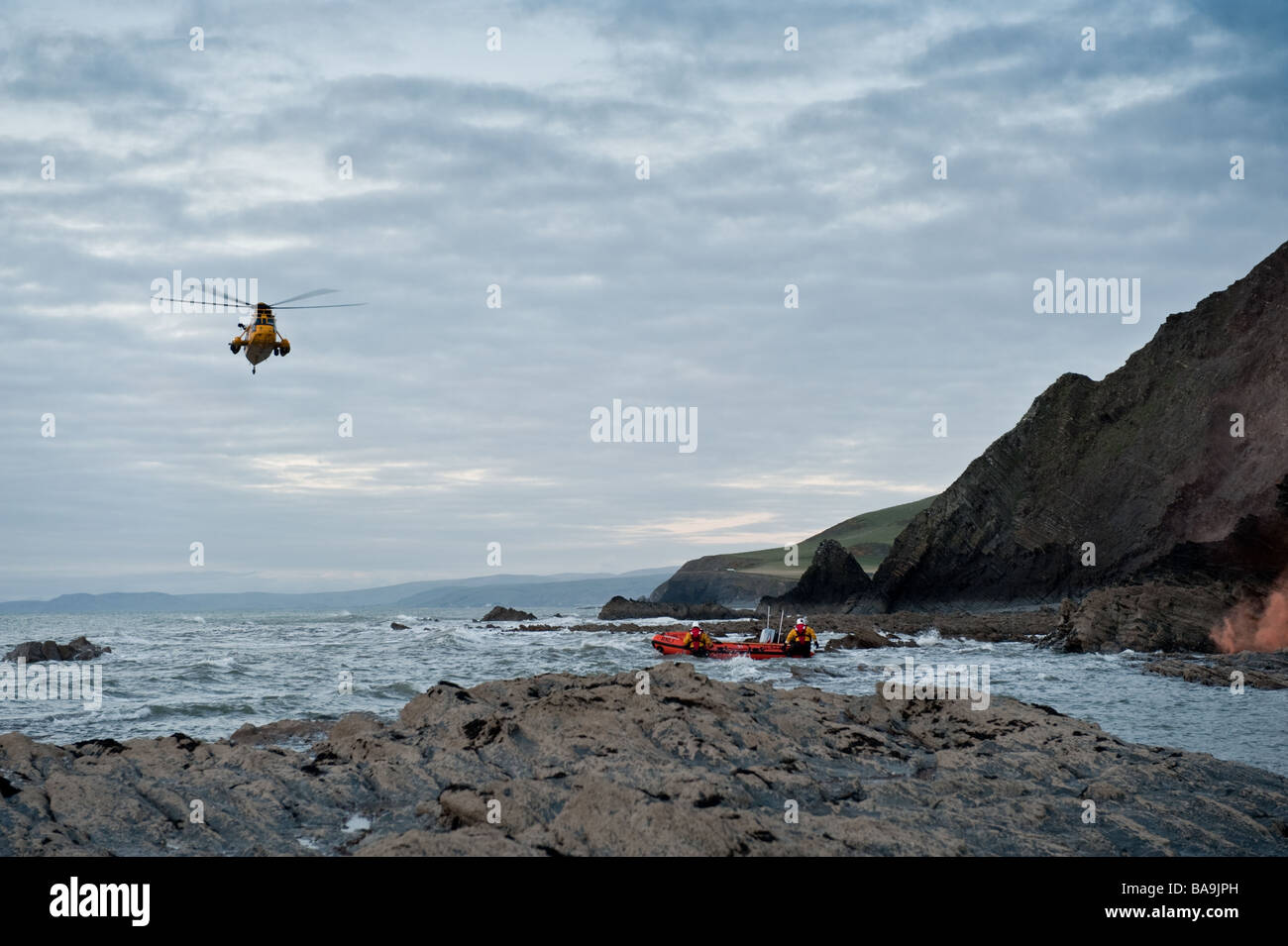 A Sea King helicopter and RNLI inshore lifeboat rescuing a young man who had fallen off the cliffs at Aberystwyth - Stock Image