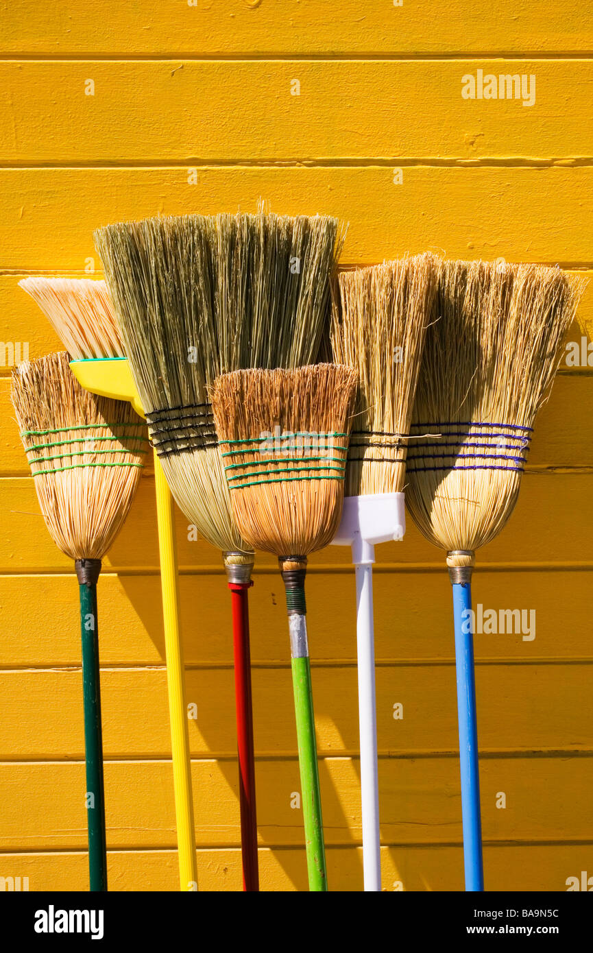 Brooms leaning against yellow wall - Stock Image