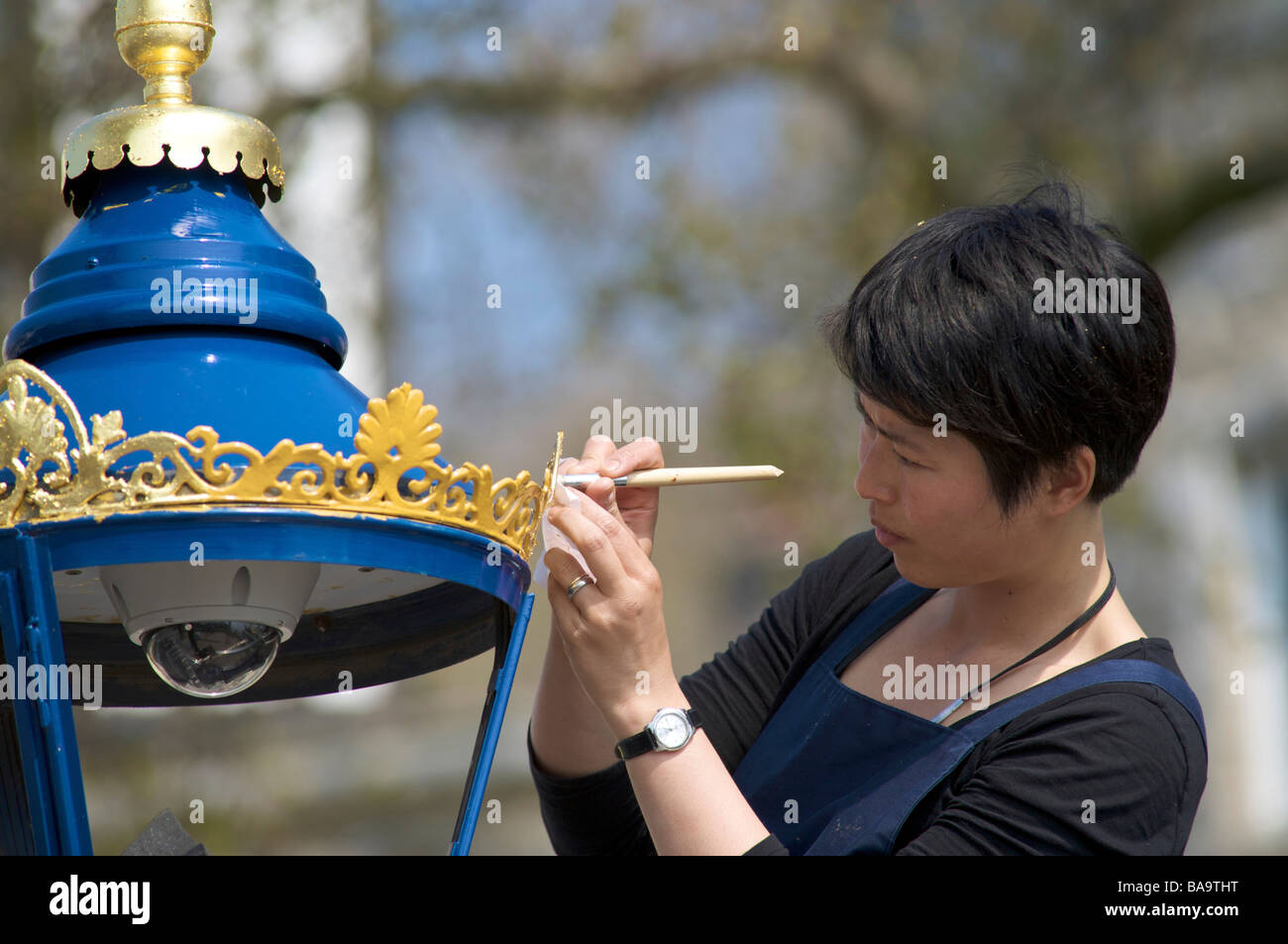 Applying gold leaf to lamposts close to the Tower of London, London, England - Stock Image