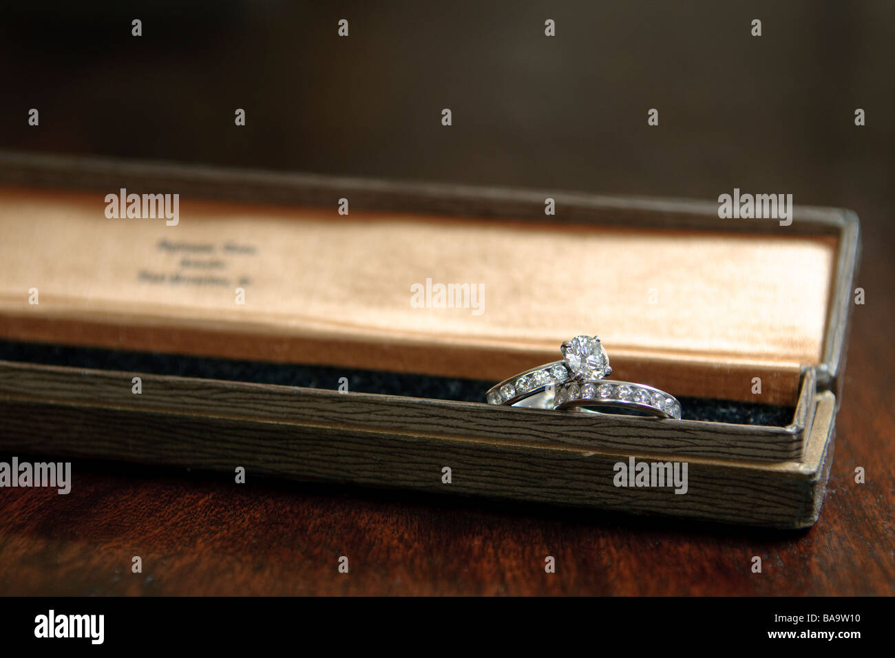 A diamond and platinum womens wedding ring set resting in a long jewelry box on a wooden table - Stock Image