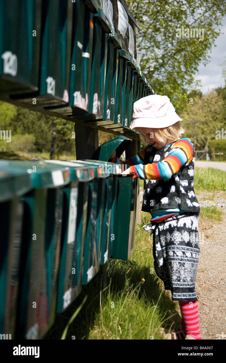 A girl looking into a letterbox, Varmdo, Sweden. - Stock Image