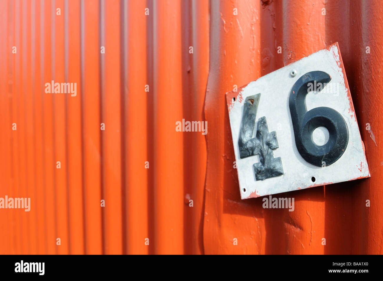 A numer sign on a red wall - Stock Image