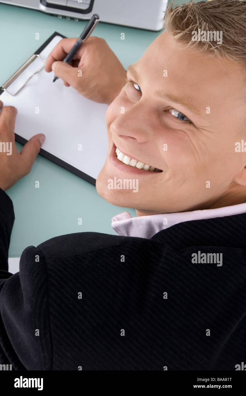 back pose of smiling employee with pen and writing board - Stock Image