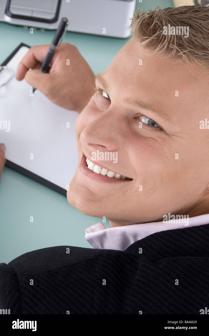 back pose of smiling man with pen and writing board - Stock Image