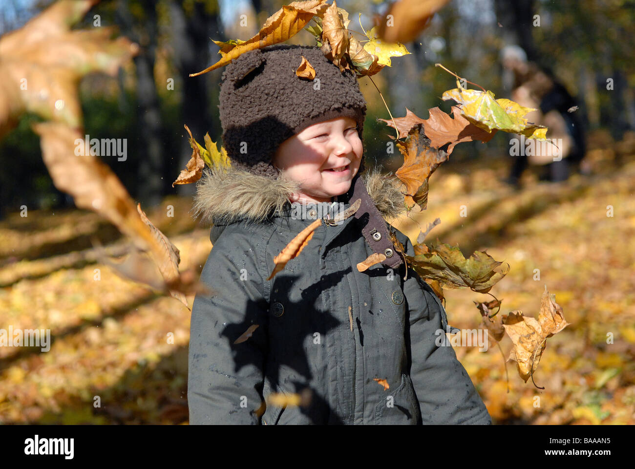 Toddler in the park in the autumn - Stock Image