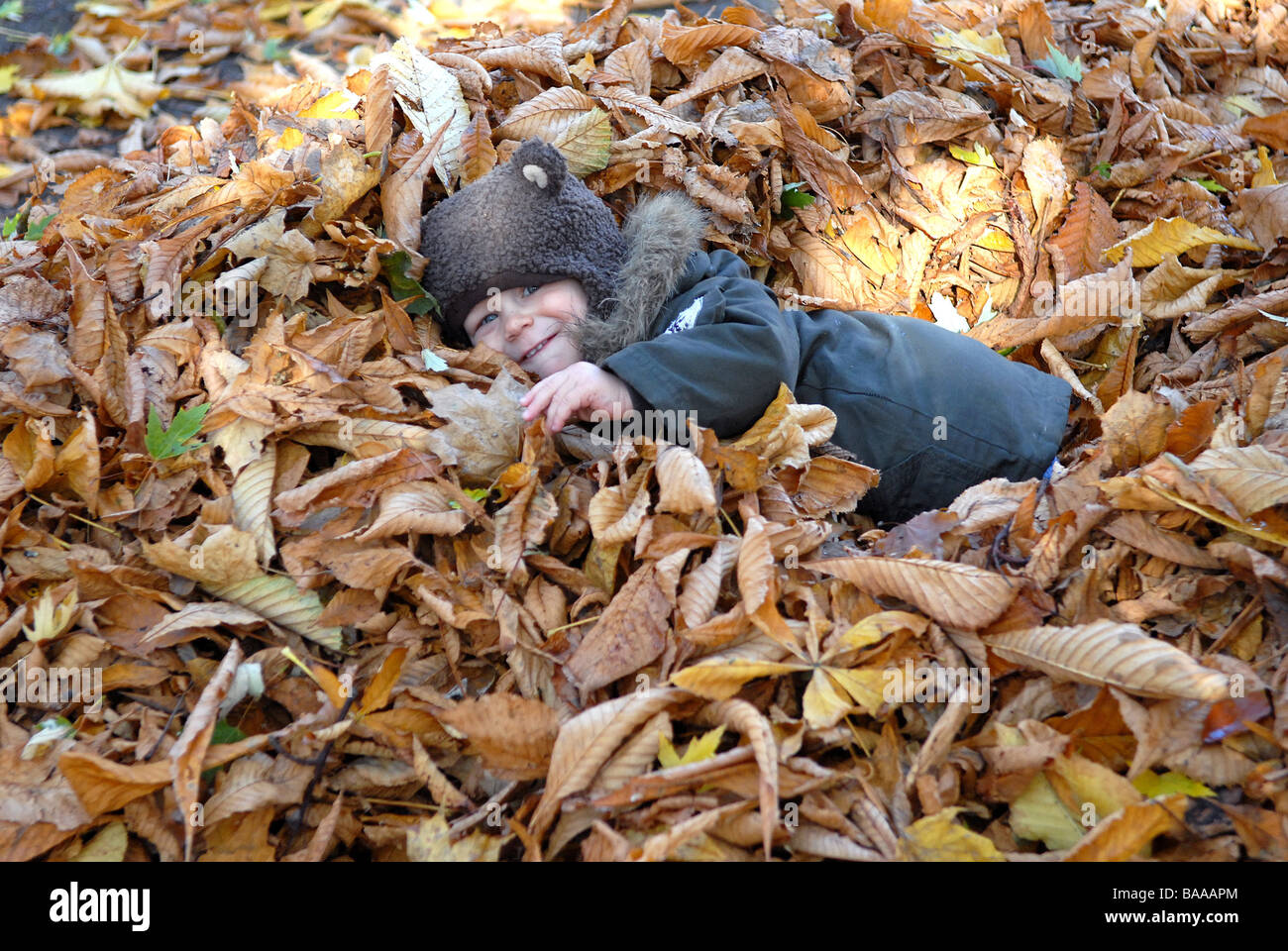 Toddler in the park in the autumn Stock Photo