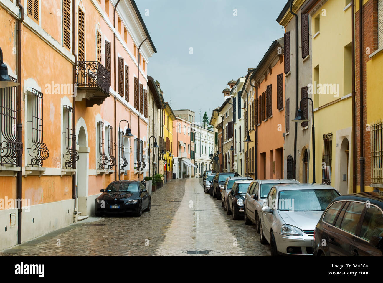 photograph of colourful italian street in ravenna with parked cars - Stock Image