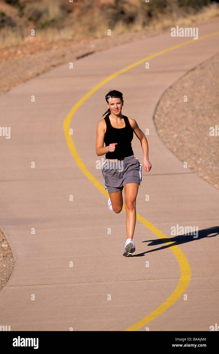 Woman running on paved trail in St. George, Utah. - Stock Image