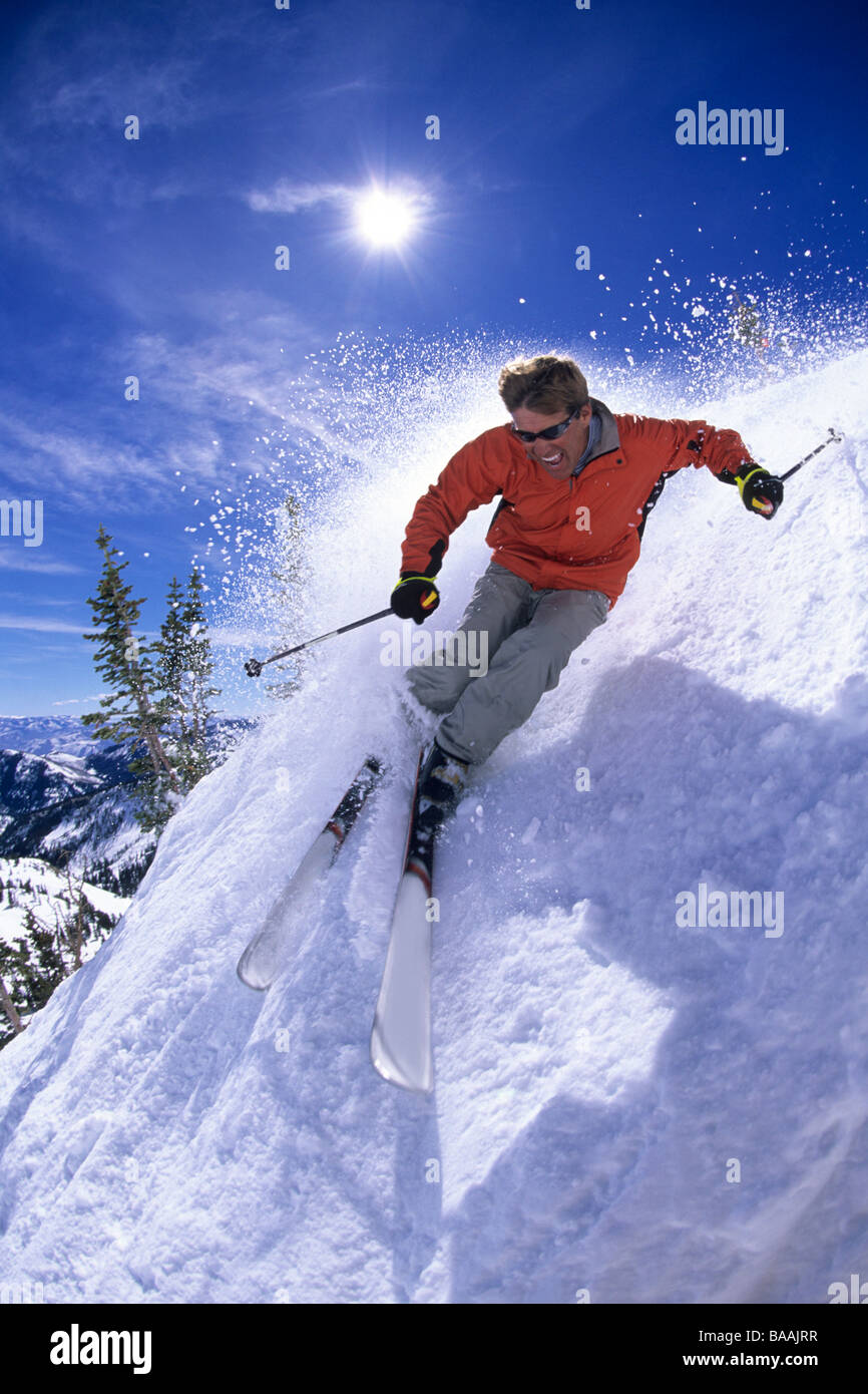 Man spring skiing on a sunny day in Utah. - Stock Image