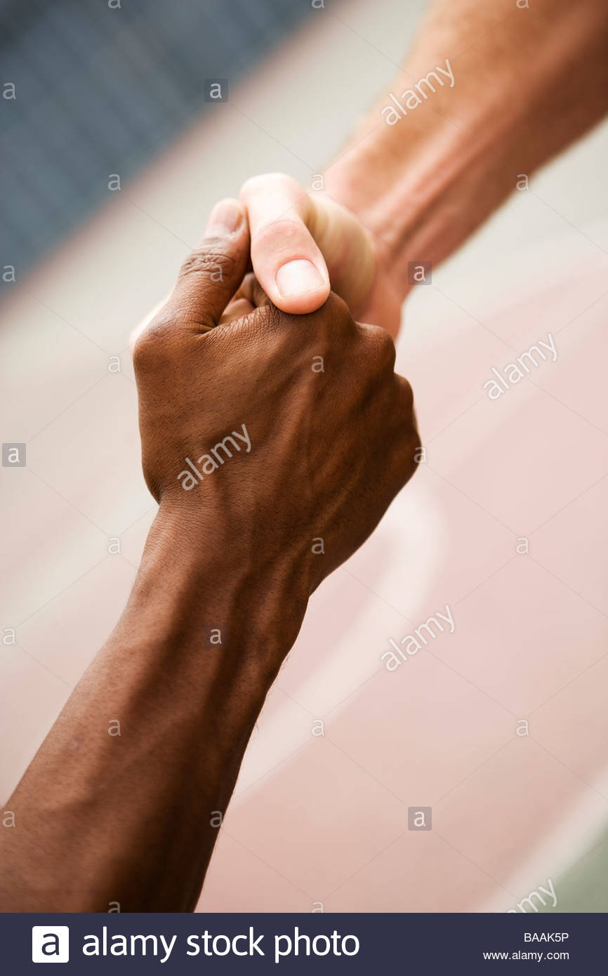 Two basketball players shake hands during a pickup game in an urban setting in Long Beach, California. - Stock Image
