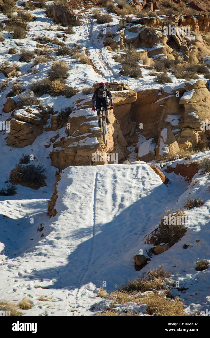 Mountain biker jumping with snowy landing in Moab, Utah. - Stock Image