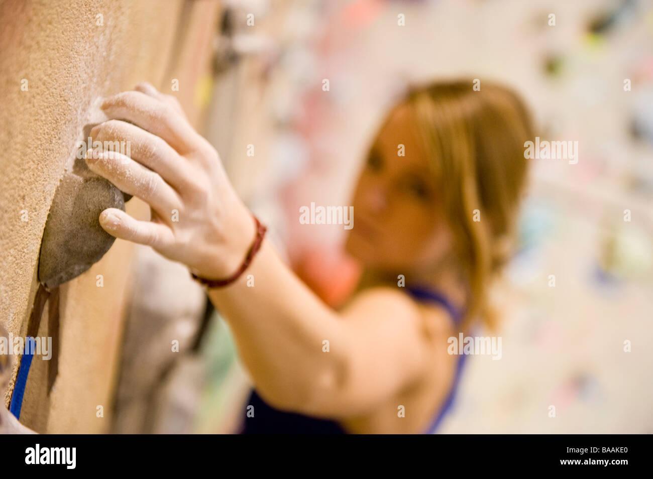 A woman rock climbing indoors at Estes Park, Colorado. - Stock Image