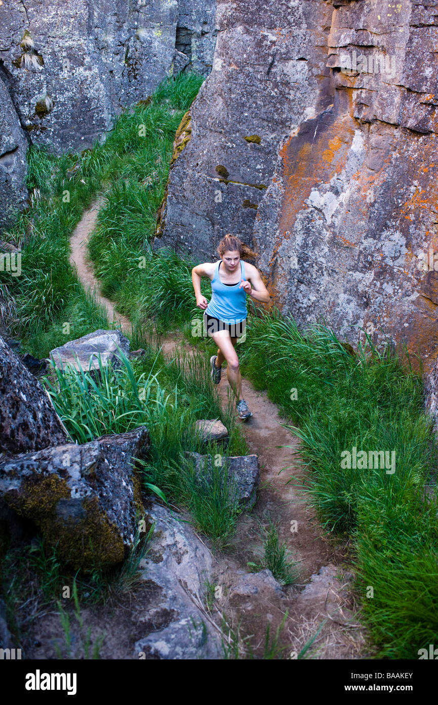 One woman running through Crack In the Ground, a volcanic fissure near Christmas Valley, Oregon. - Stock Image