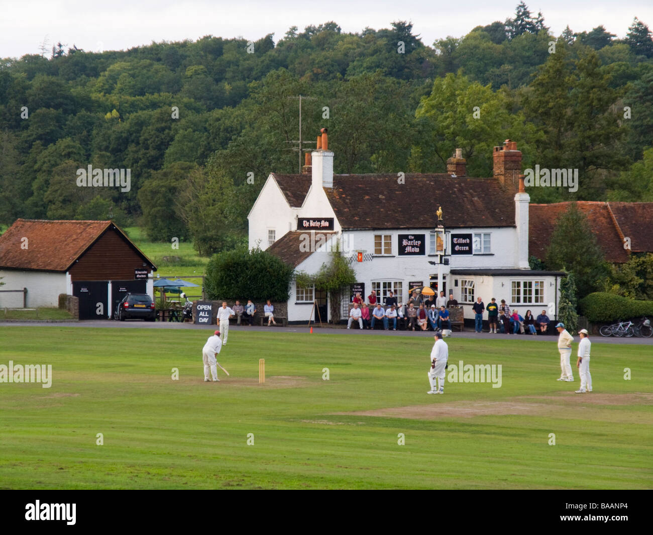 Tilford Surrey England UK Playing cricket on the village green outside the Barley Mow country pub in summer - Stock Image