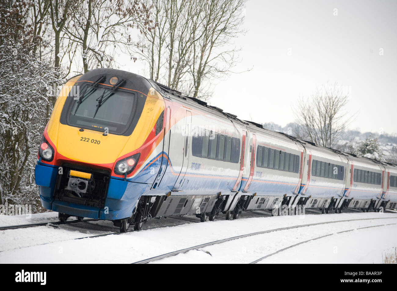Class 222 Meridian train in East Midlands Trains livery travelling through snow in the Leicestershire countryside - Stock Image