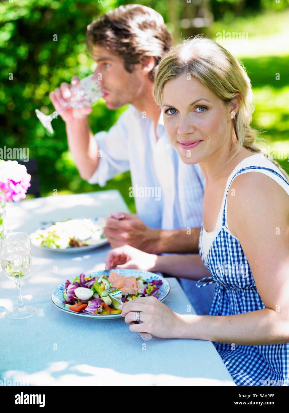 Couple having dinner in the garden, Stockholm, Sweden. - Stock Image