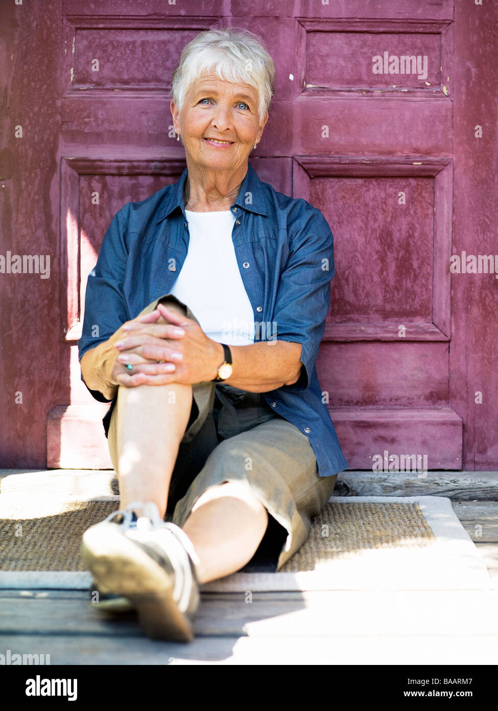 A woman sitting in front of a door, Stockholm, Sweden. - Stock Image