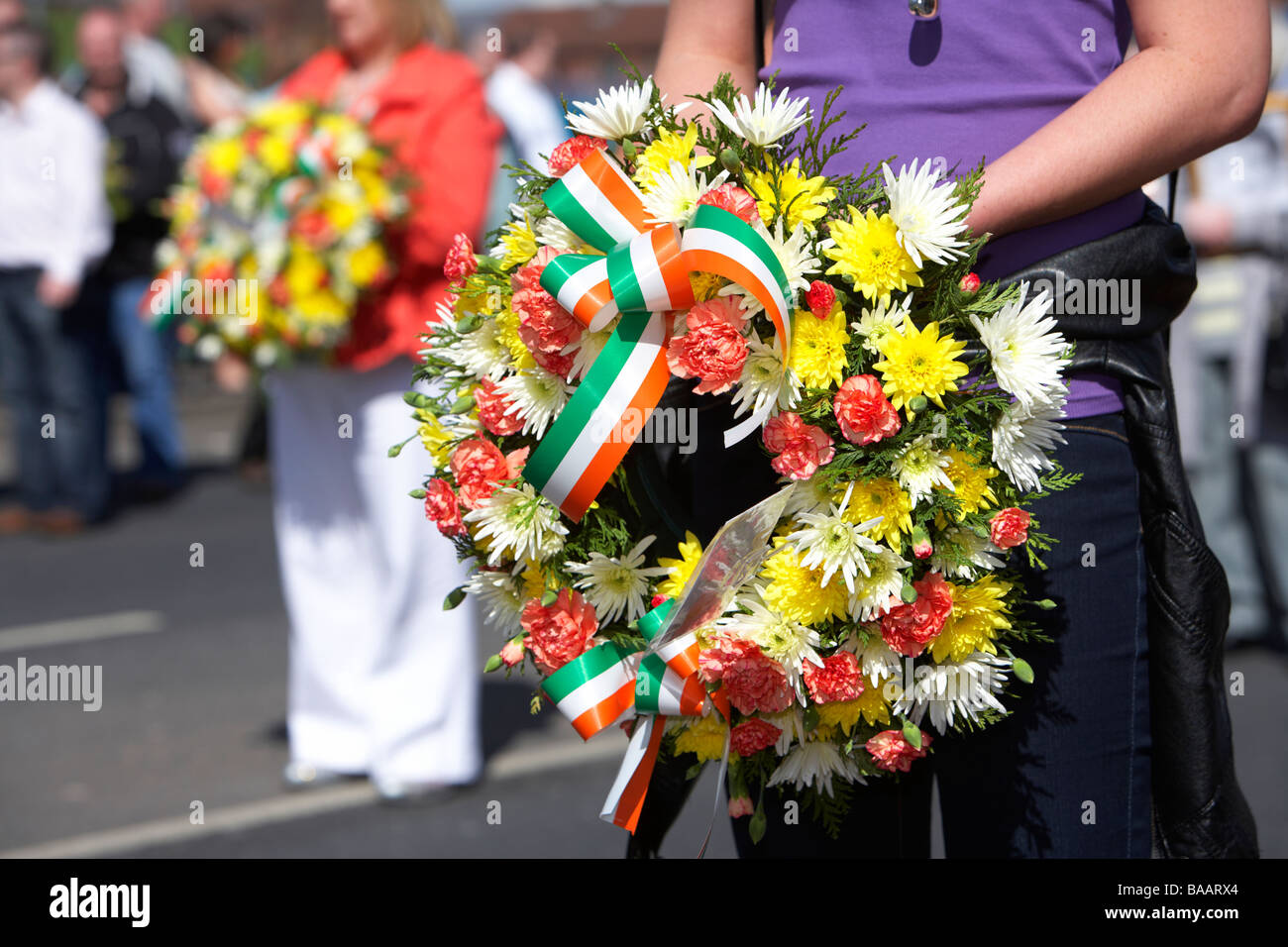 women carry floral wreaths commemorating irish dead easter Sunday Easter Rising Commemoration Falls Road Belfast - Stock Image