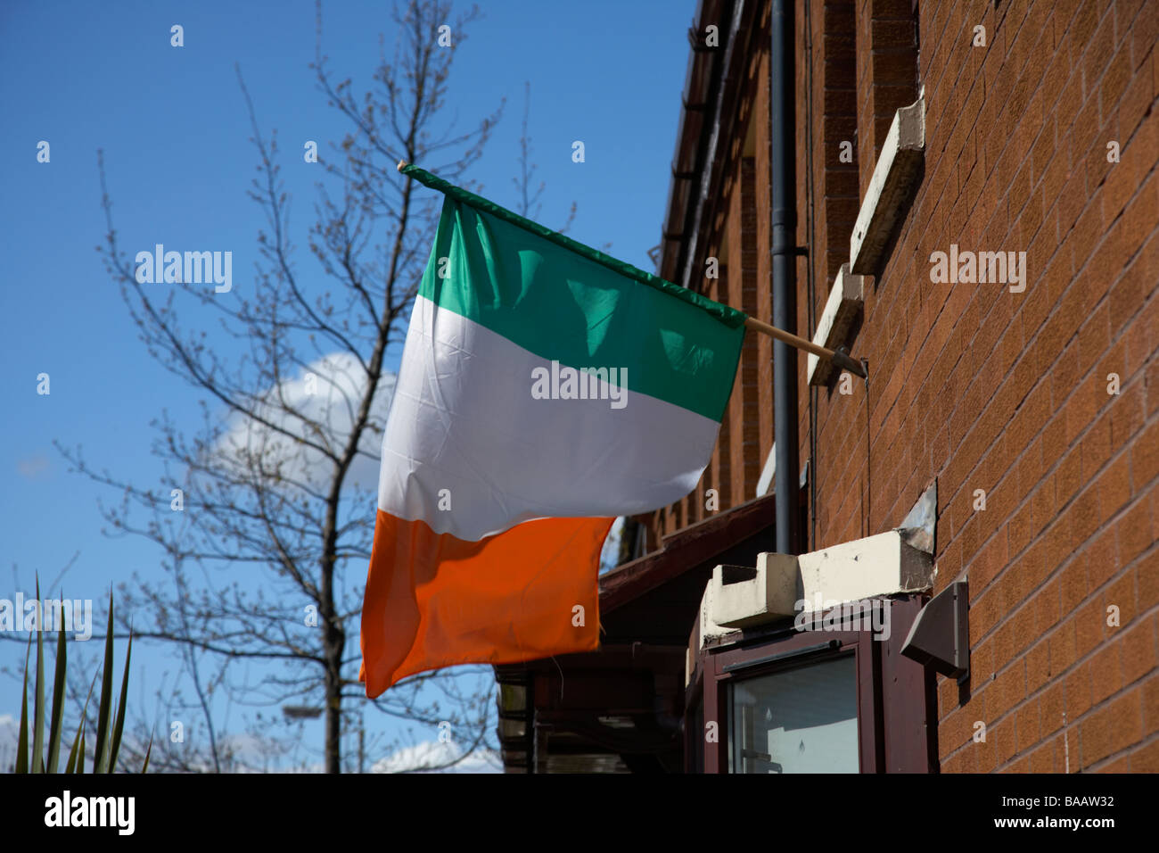Irish tricolour green white and orange flag flying from a house in a republican area of belfast northern ireland - Stock Image