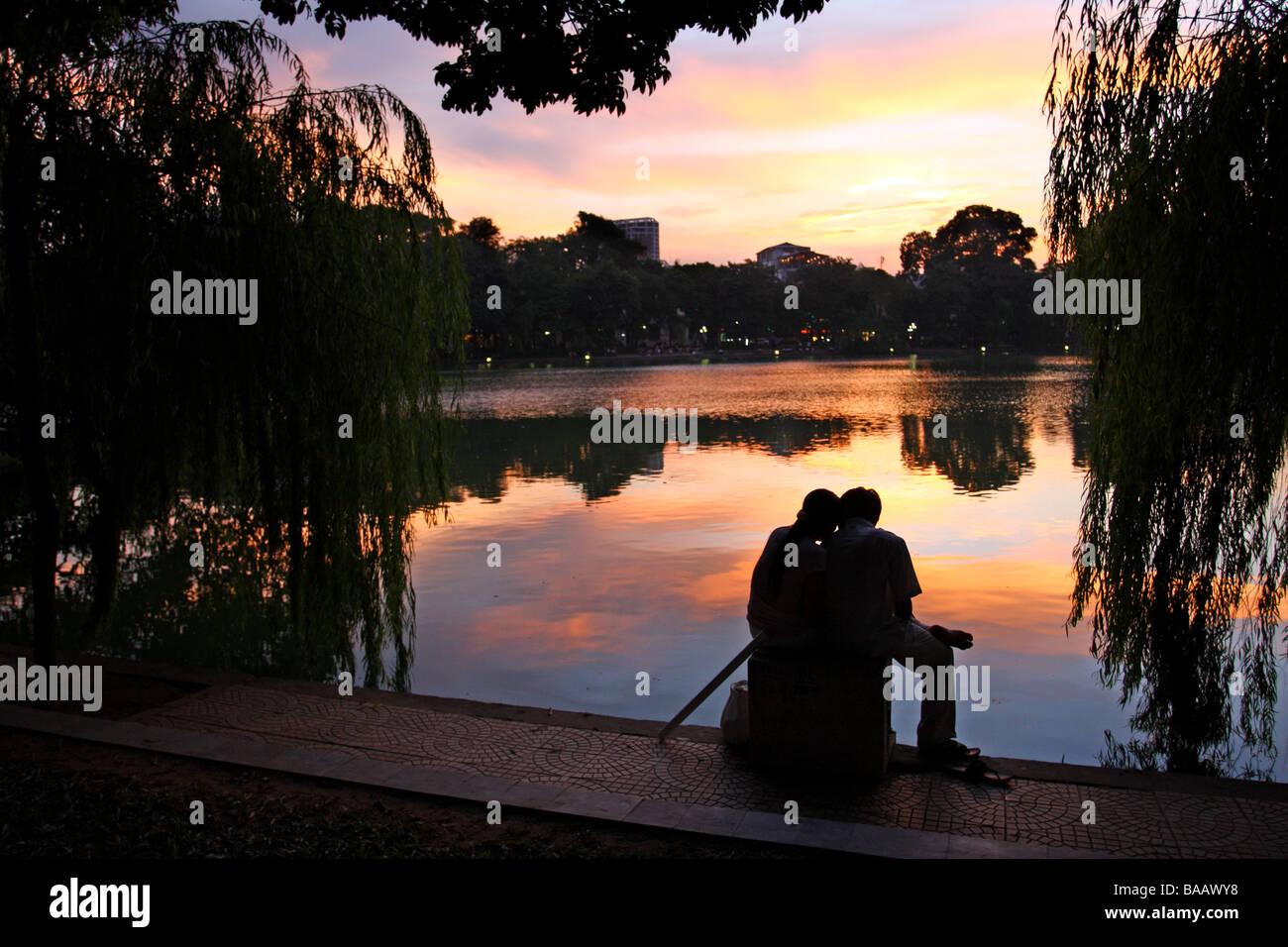 Street scene. Couple sitting in front of a beautiful sunset on Hoan Kiem lake. Hanoi, Vietnam - Stock Image