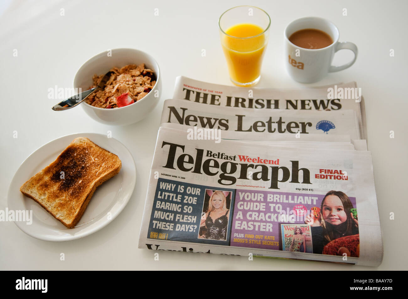 Main Belfast, Northern Ireland morning newspapers beside a healthy breakfast - Stock Image
