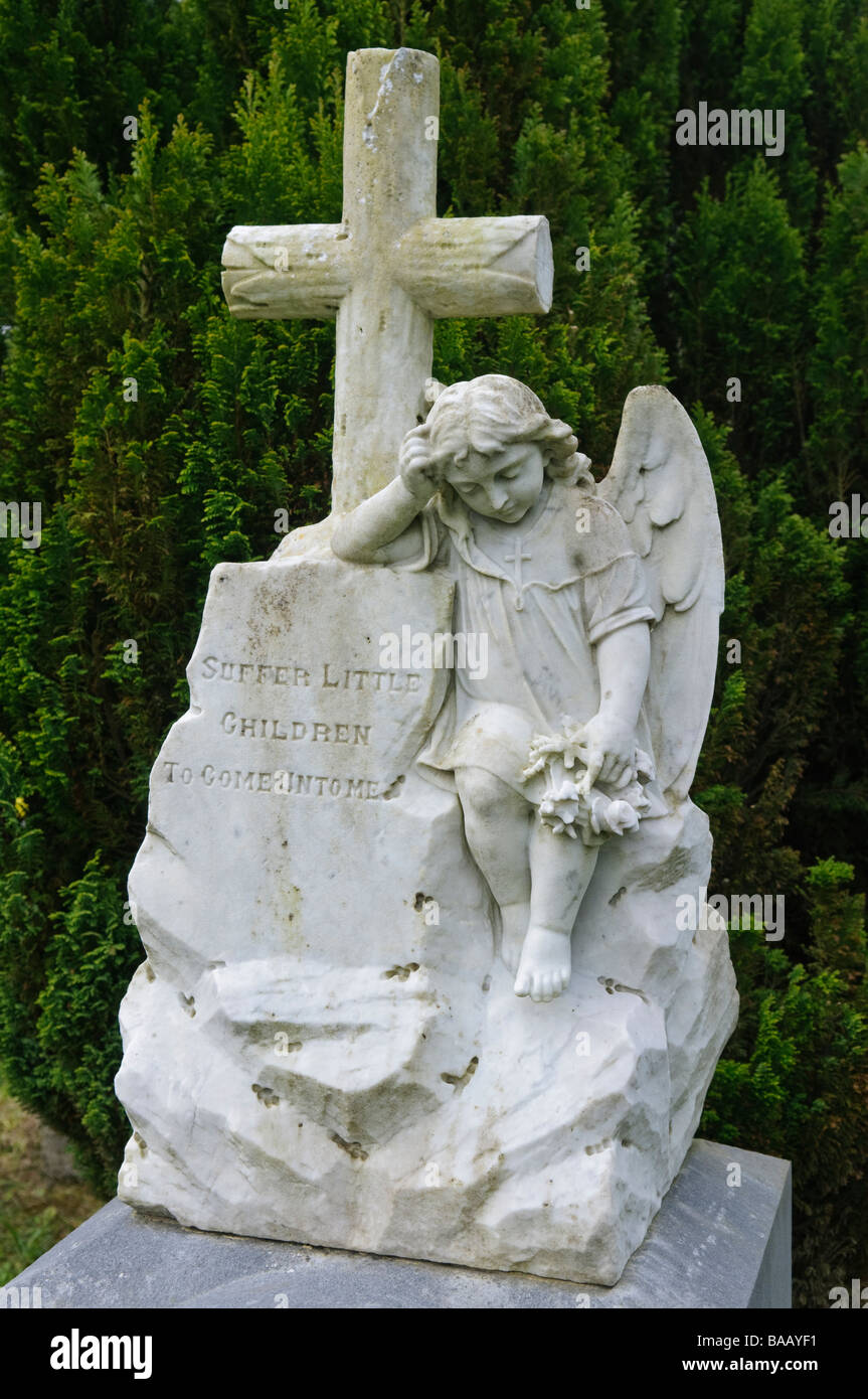 Statue of an angel beside a cross with the inscription 'Suffer Little Children to Come Onto Me' - Stock Image