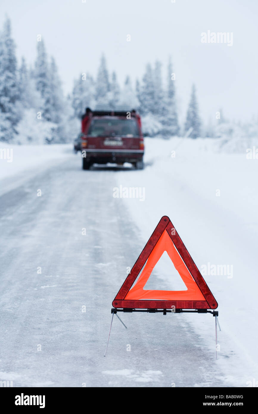 A warning triangle on a country road in the winter, Sweden. Stock Photo