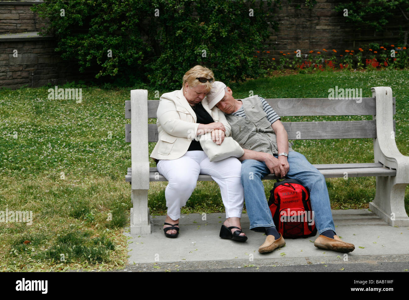 Older couple take a cat nap on a bench at the Brooklyn Botanic Gardens in Brooklyn NY - Stock Image