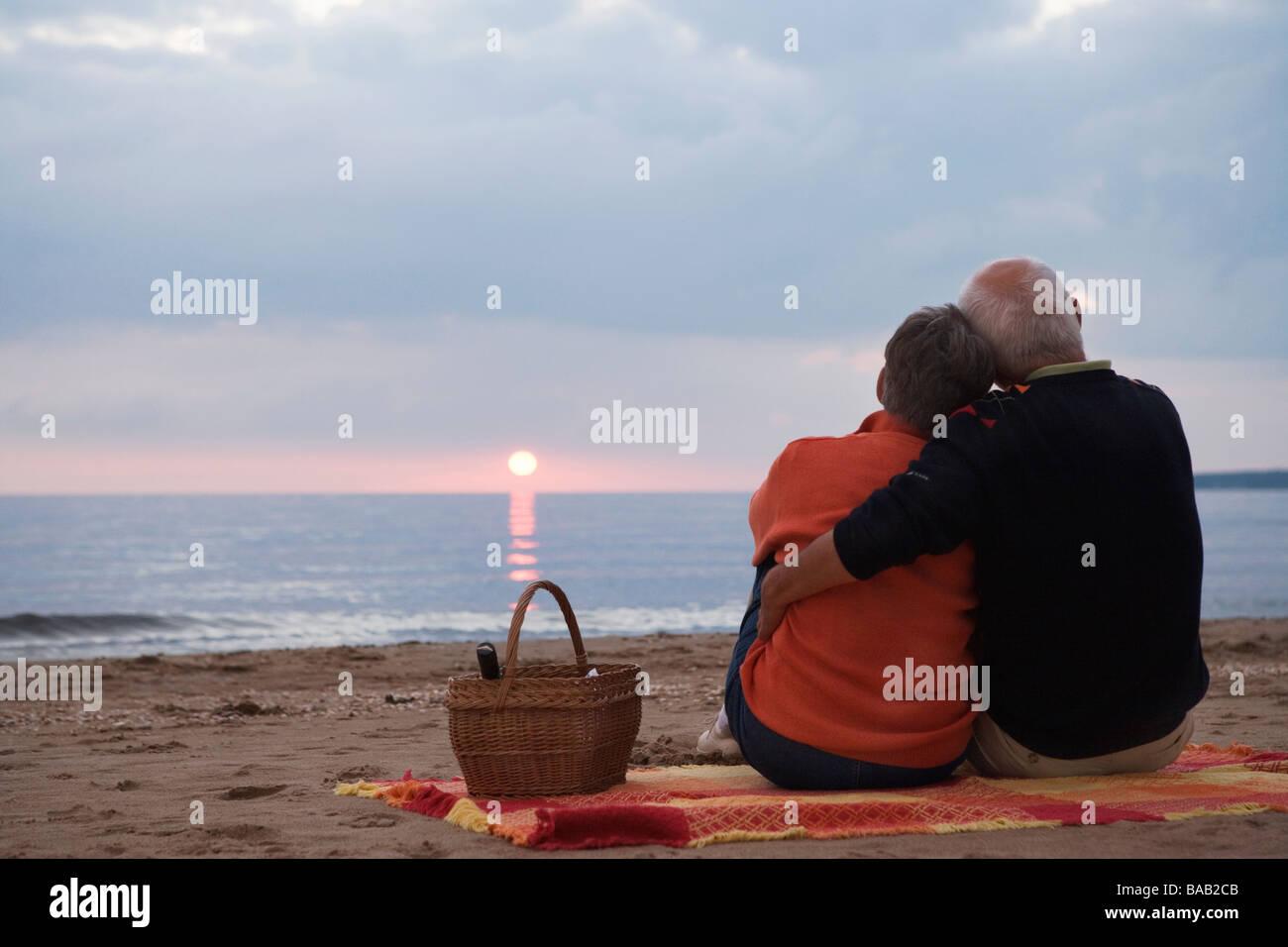 An elderly couple sitting on a beach, Skane, Sweden. - Stock Image