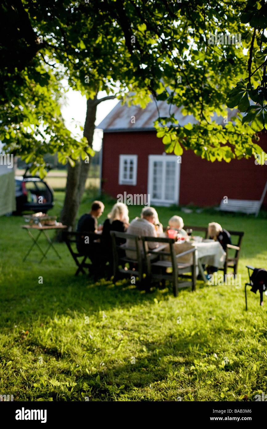 A family having dinner in the garden, Gotland, Sweden. - Stock Image