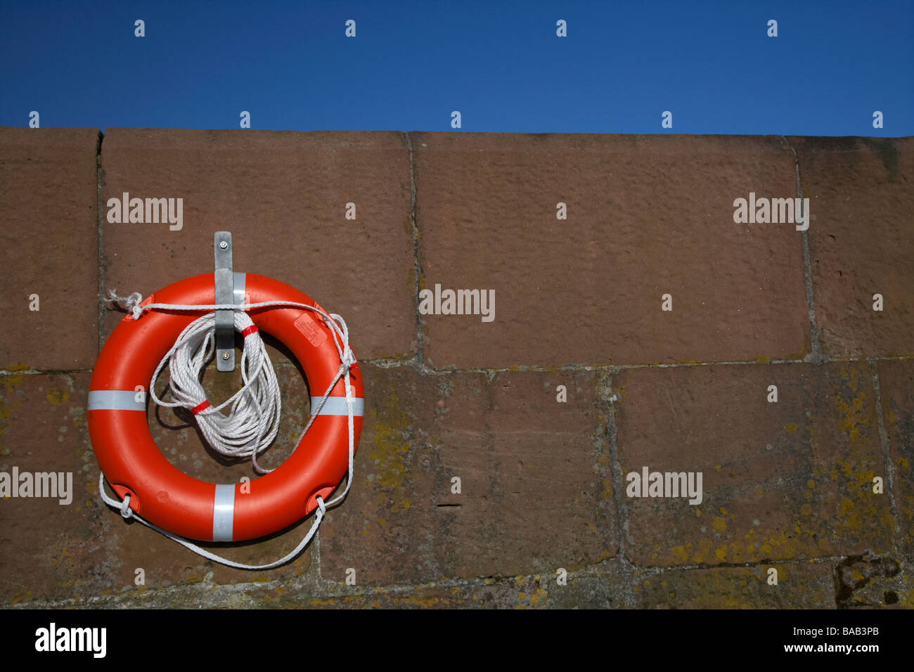 brand new bright red lifebelt with white rope hanging on a hanger on brown harbour wall with blue sky - Stock Image