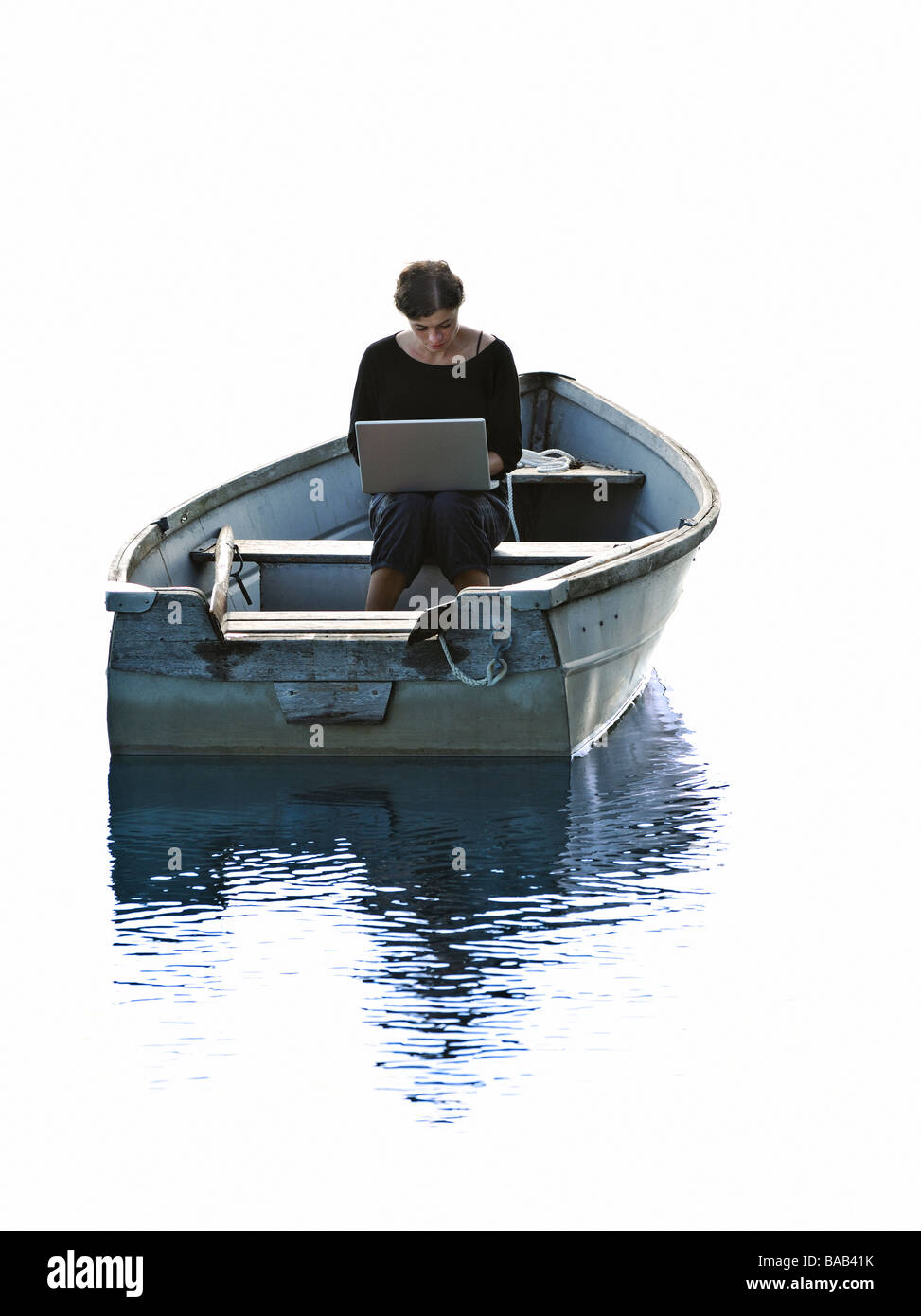 A woman using a laptop sitting in a rowing-boat, Stockholm archipelago, Sweden. - Stock Image